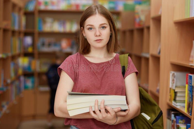 Netter intelligenter weiblicher Knabe hält Buch, trägt Rucksack, aufwirft in der Schulbibliothek, sucht nach notwendigem Material lizenzfreie stockfotografie