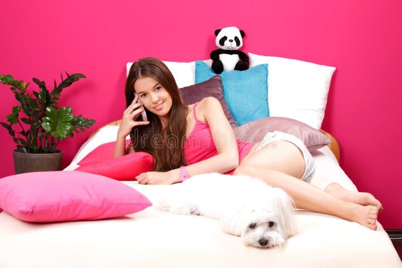 Netter Jugendlicher, der einen Telefonaufruf in ihrem Raum bildet stockfotos