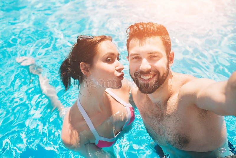 Netter jugendlicher Kerl und Dame, die während Swimmingpool im Freien stillsteht Paare im Wasser Kerle tun Sommer sephi stockfotos