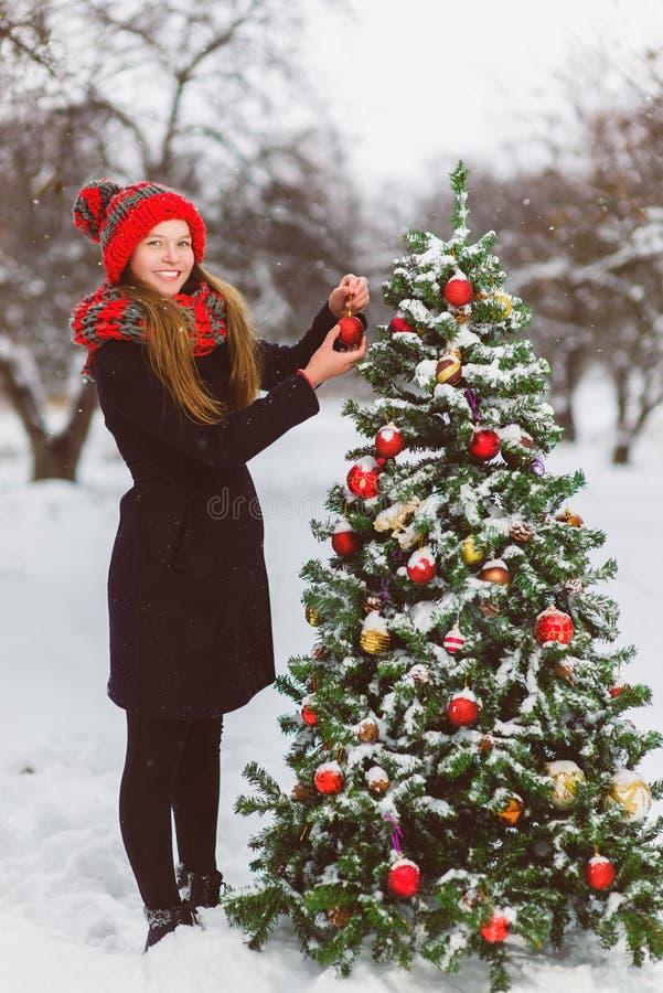 Netter Jugendlicher oder Mädchen, die den Weihnachtsbaum im Freien verziert lizenzfreies stockfoto