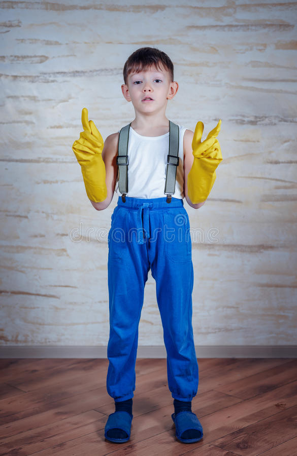 Netter Junge in übergroßen Gummihandschuhen stockfoto