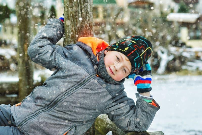 Netter Junge auf einem Winterweg, gekleidet in einer Jacke und in einem Hut lizenzfreie stockfotografie