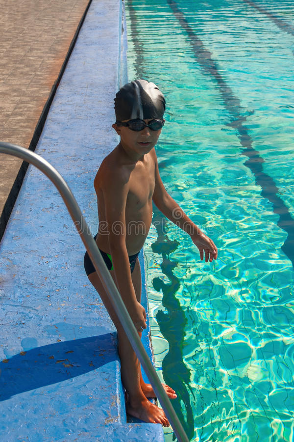 Netter Junge bereit, im Sportschwimmen poolb zu tauchen, das auf Grenze nahe Poolleiter steht lizenzfreie stockfotos