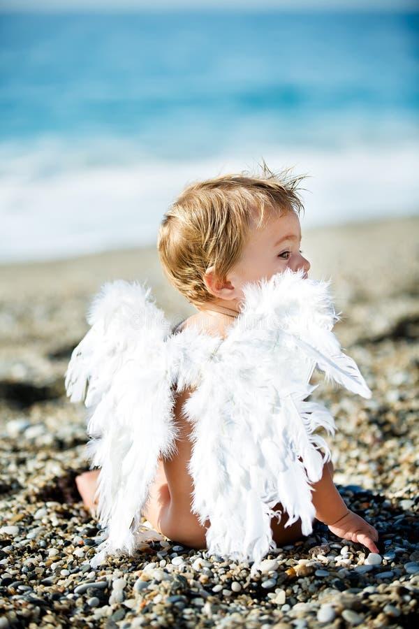 Netter Junge, der auf dem Strand sitzt lizenzfreies stockbild
