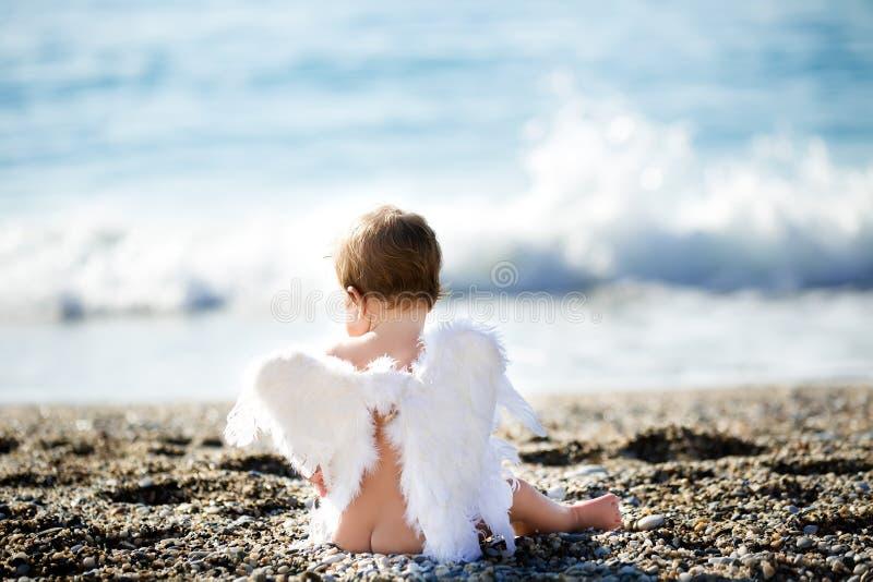 Netter Junge, der auf dem Strand sitzt lizenzfreie stockfotografie
