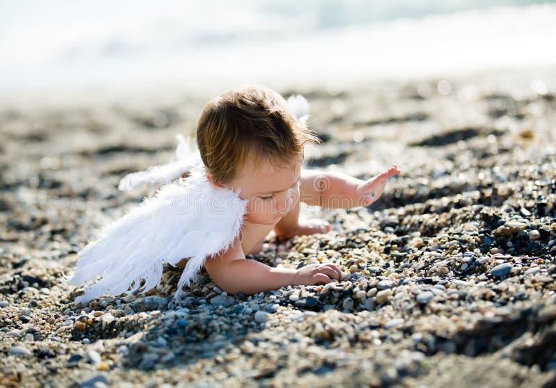 Netter Junge, der auf dem Strand sitzt stockbild