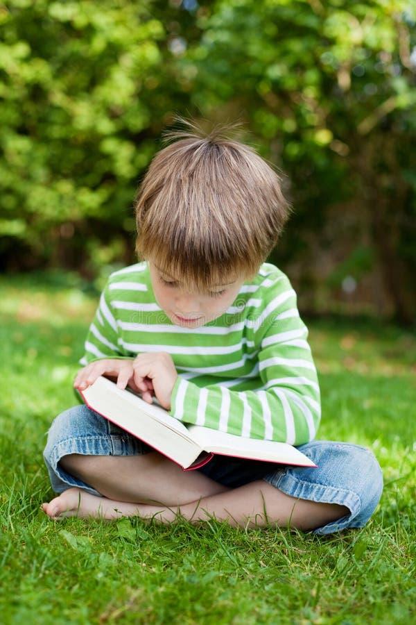 Netter Junge, der auf Gras und dem Ablesen sitzt lizenzfreie stockfotos