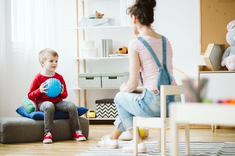 Netter Junge, der auf Puff sitzt und blauen Ball w?hrend ADHD-Therapie h?lt stockfotos