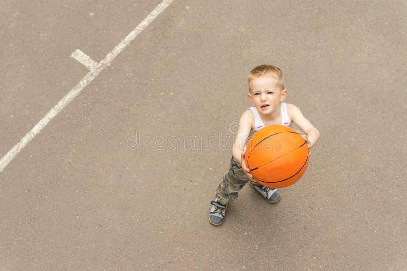 Netter Junge, der den Basketball auf das Netz abzielt stockbilder