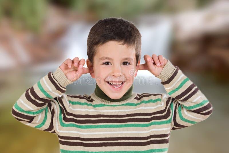 Netter Junge, der die Ohren bedeckt lizenzfreies stockbild