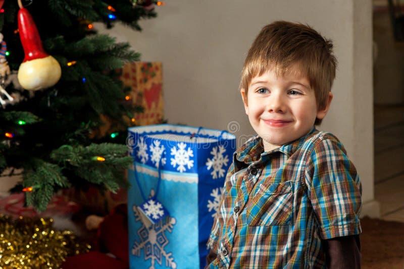 Netter Junge, der durch einen Weihnachtsbaum mit Geschenk-Taschen Smirking ist stockbild