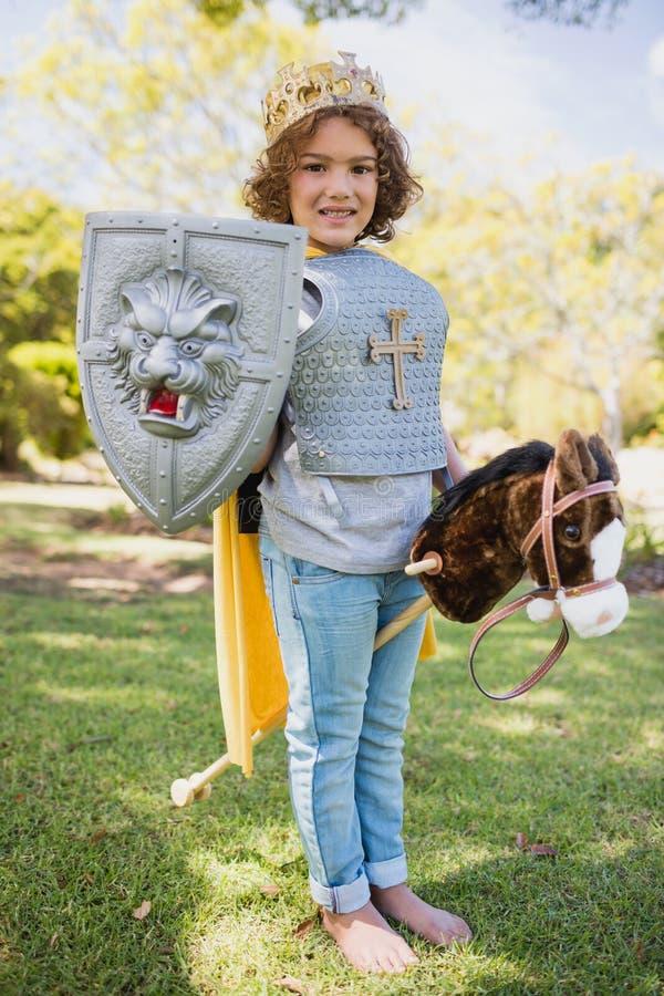 Netter Junge, der, ein Ritter zu sein steht und vortäuscht lizenzfreie stockbilder