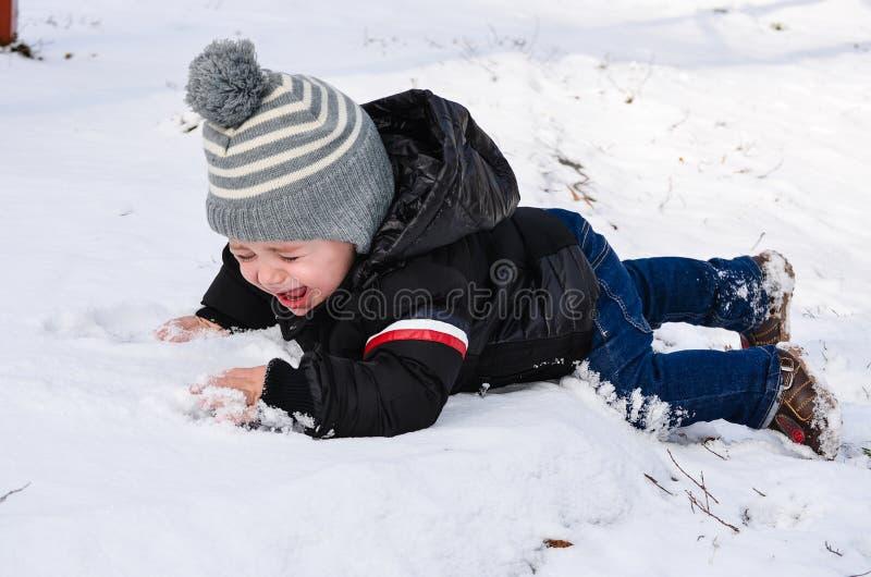 Netter Junge, der im Schnee schreit lizenzfreies stockbild