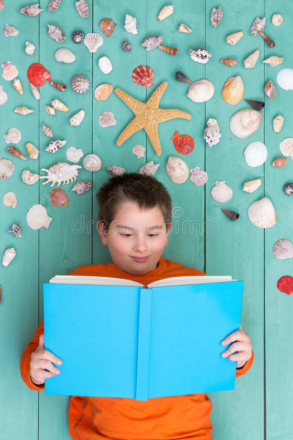 Netter Junge, der leeres Buch nahe Muscheln liest lizenzfreies stockfoto