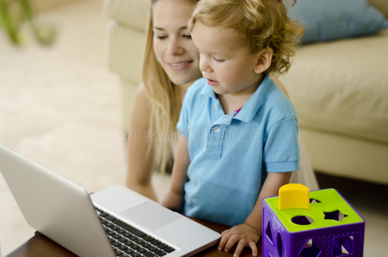 Netter Junge, der lernt, einen Computer zu benutzen stockfoto