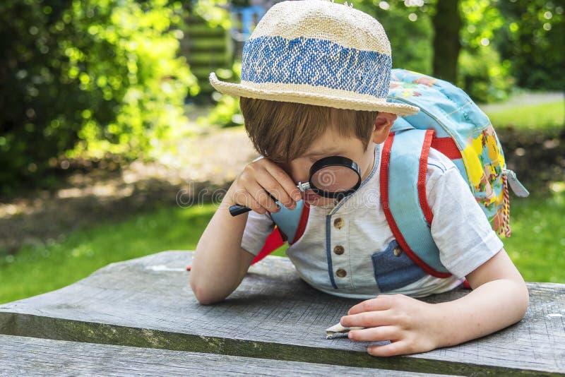 Netter Junge, der mit einer Lupe spielt lizenzfreie stockbilder