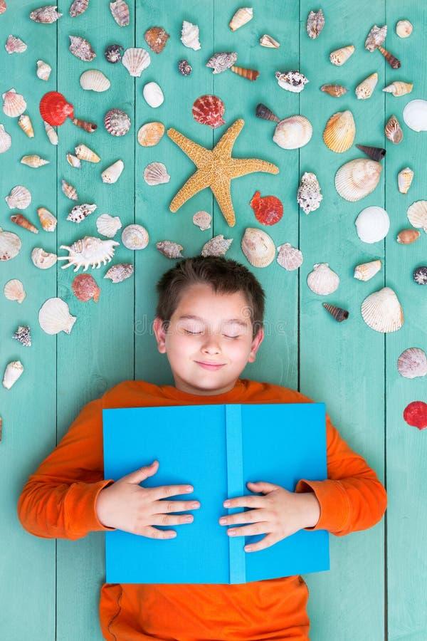 Netter Junge, der nahe Seeoberteilen niederlegt lizenzfreies stockbild
