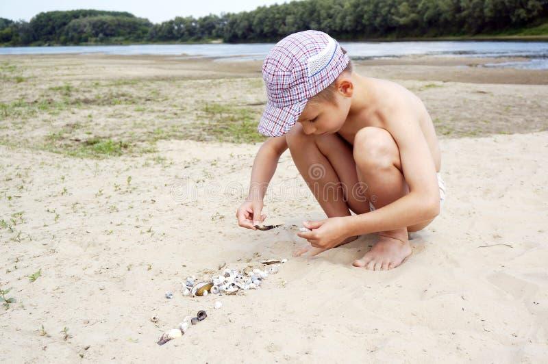 Netter Junge, der am Strand mit Oberteilen spielt lizenzfreies stockfoto