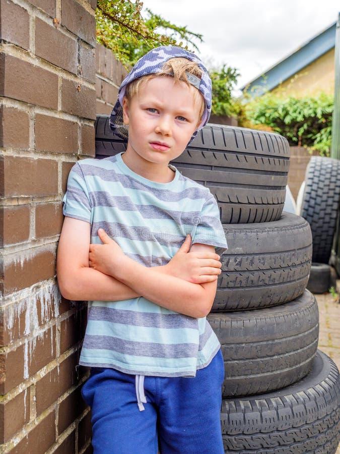 Netter Junge der Tagesansicht kleines Kinder, dernahe bei Stapel benutzten Reifen über Ziegelsteinenglischwand aufwirft lizenzfreie stockfotografie