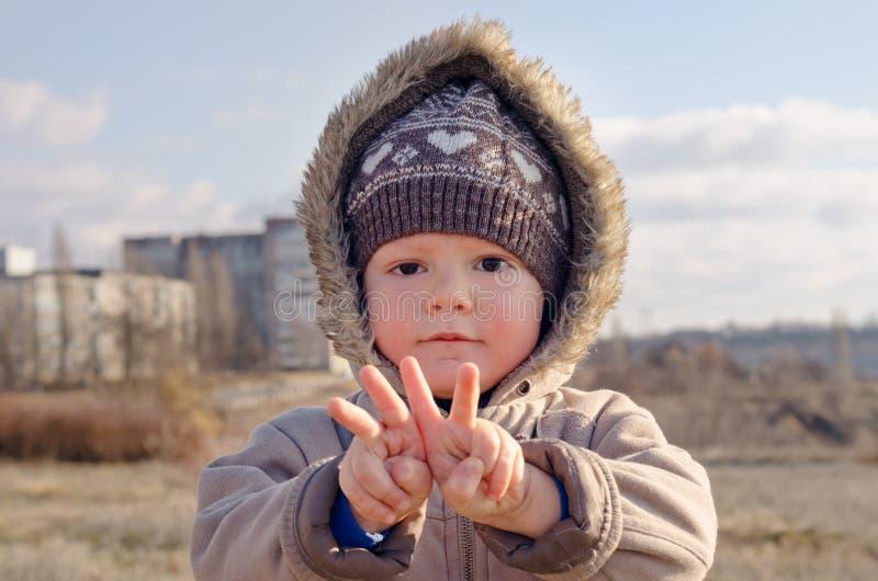 Netter Junge, der V-Zeichengesten macht lizenzfreie stockfotografie