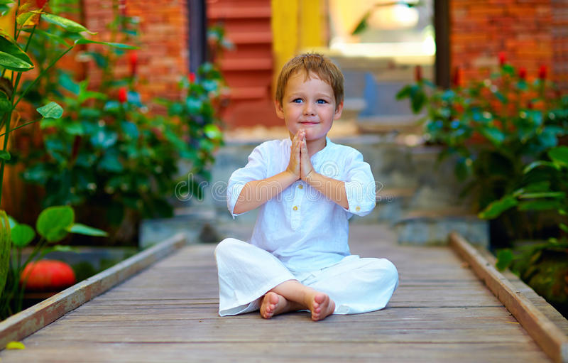 Netter Junge, der versucht, innere Balance in der Meditation zu finden lizenzfreie stockbilder