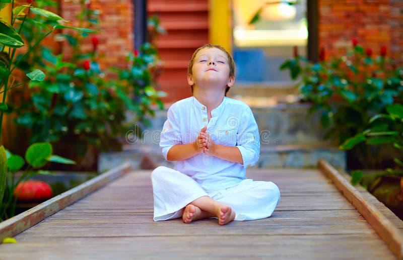 Netter Junge, der versucht, innere Balance in der Meditation zu finden stockfoto