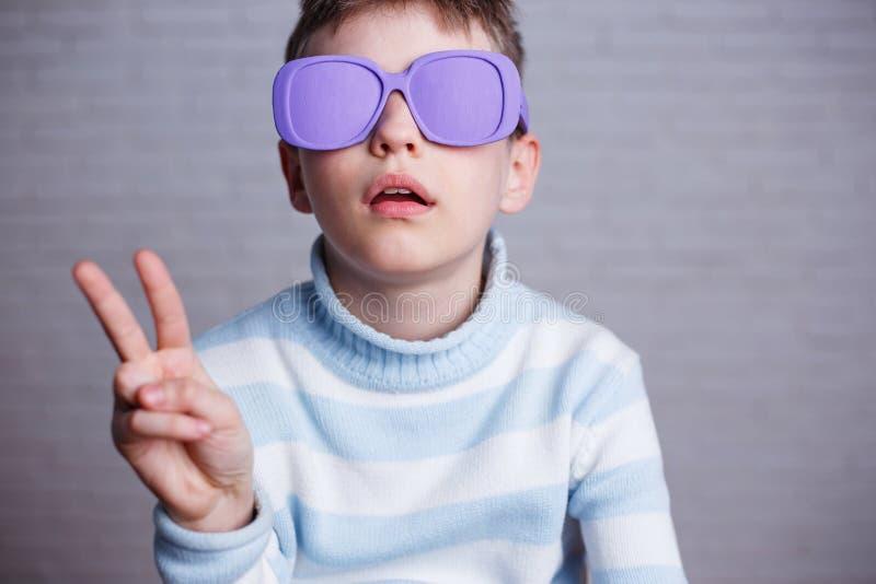 Netter Junge in der violetten Sonnenbrille mit den undurchsichtigen Linsen, die Sieg zeigen lizenzfreie stockfotos