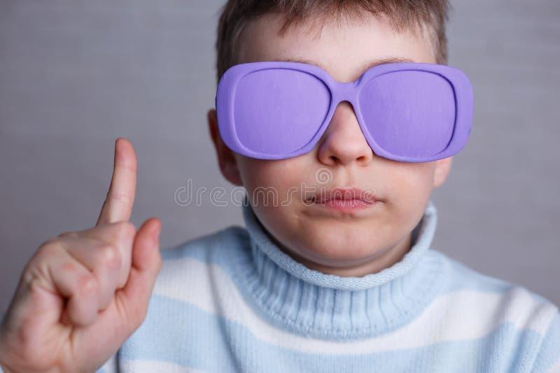 Netter Junge in der violetten Sonnenbrille mit undurchsichtigen Linsen aufwärts zeigend lizenzfreie stockbilder