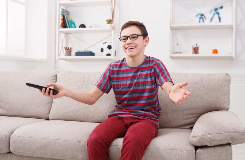 Netter Junge, der zu Hause lustige Fernsehshow aufpasst stockfotos