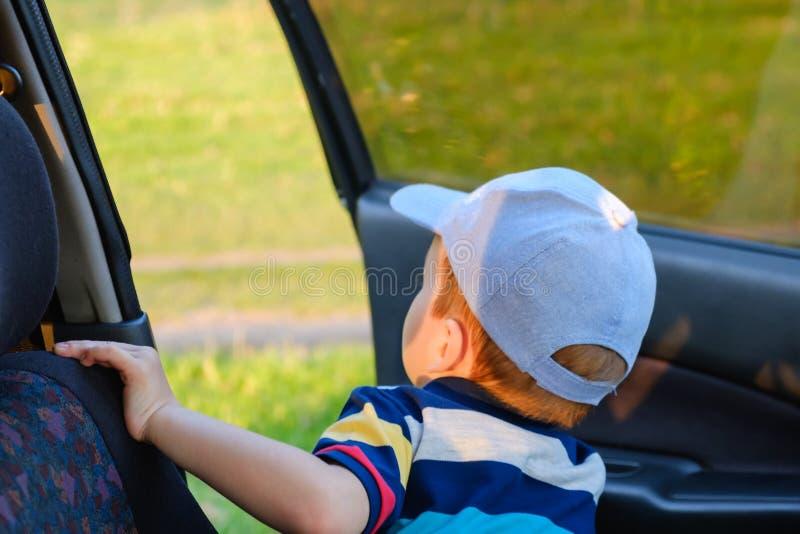 Netter Junge des Porträts Kinder, derim Autositz sitzt Kindertransportsicherheit lizenzfreie stockfotos