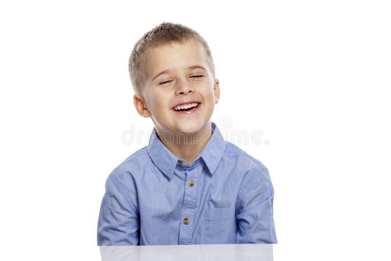 Netter Junge des schulpflichtigen Alters sitzt am Tisch und am Lachen Getrennt auf einem wei?en Hintergrund lizenzfreie stockfotografie