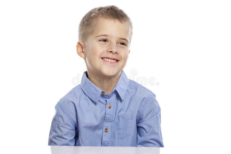 Netter Junge des schulpflichtigen Alters sitzt am Tisch und am Lachen Getrennt auf einem wei?en Hintergrund stockfoto