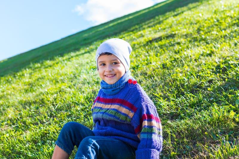 Netter Junge in einem Hut und in einer Strickjacke, die auf dem Gras sitzen lizenzfreie stockbilder