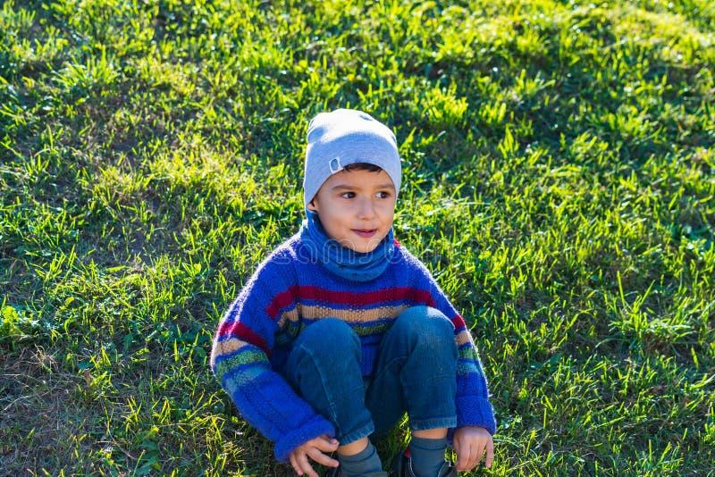 Netter Junge in einem Hut und in einer Strickjacke, die auf dem Gras sitzen stockfotografie