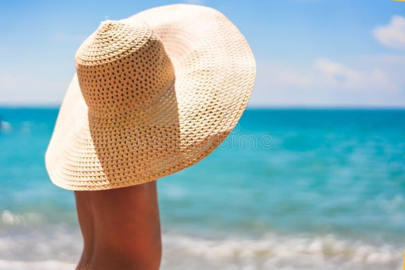 Netter Junge in einem Strohhut auf dem Strand, der auf dem Meer schaut stockfoto