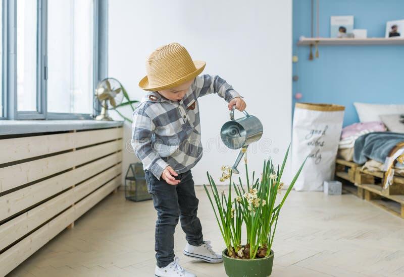 Netter Junge im Strohhut mit einer Gießkanne Bewässerungsanlage lizenzfreie stockfotos