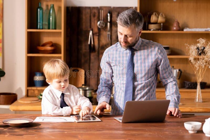 Netter Junge im weißen Hemd Geschäft mit Vater am kitch besprechend stockfoto