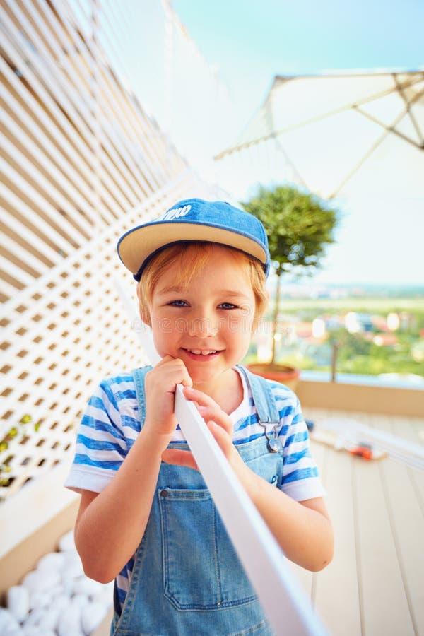 Netter Junge, Kind hilft Vater mit Erneuerung von, Pergolawand auf Dachspitzenpatiozone wodden lizenzfreie stockfotos