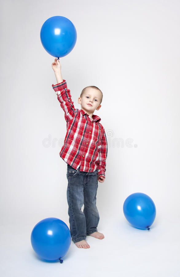 Netter Junge mit blauen Ballonen stockbild