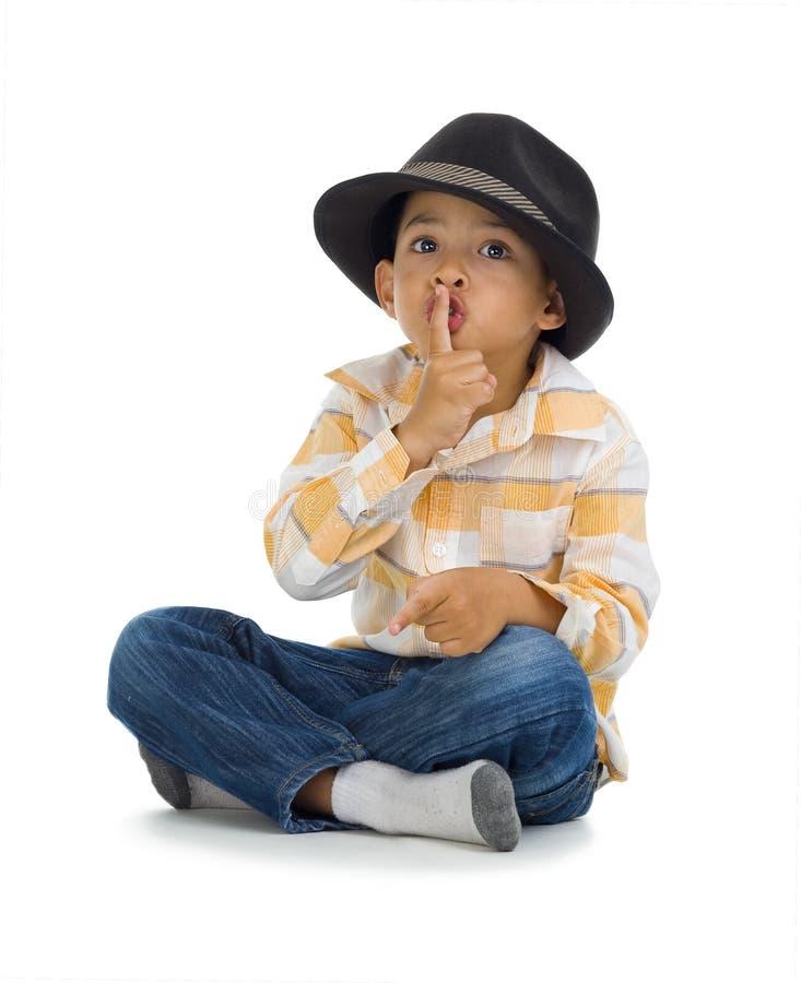 Netter Junge mit dem Finger auf seinen Lippen stockfotos
