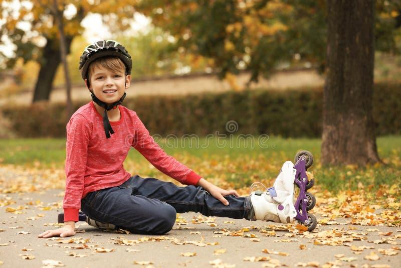 Netter Junge mit dem Rollschuhsitzen stockbilder