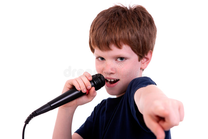 Netter Junge mit einem Mikrofon singt stockfotografie