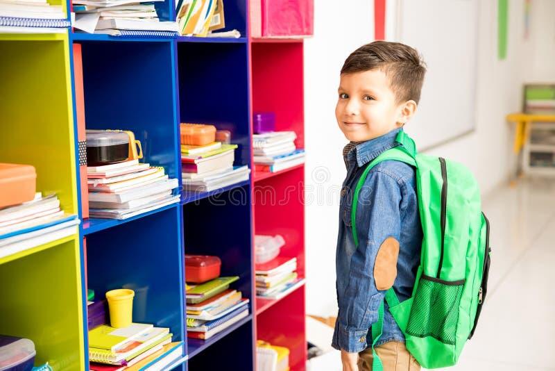 Netter Junge mit einem Rucksack in der Schule stockfotos