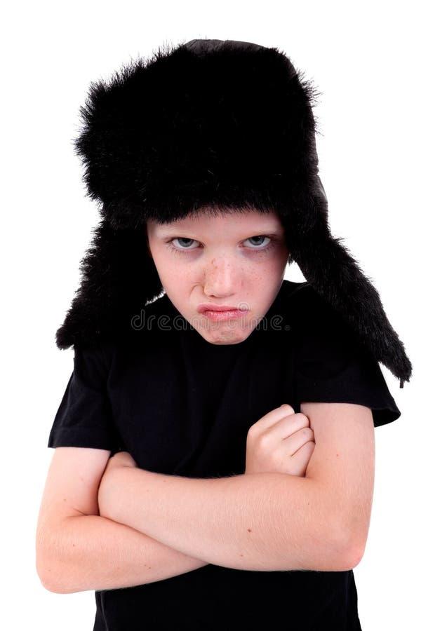 Netter Junge mit einer Schutzkappe, verärgert, wenn die Arme gekreuzt sind stockbilder