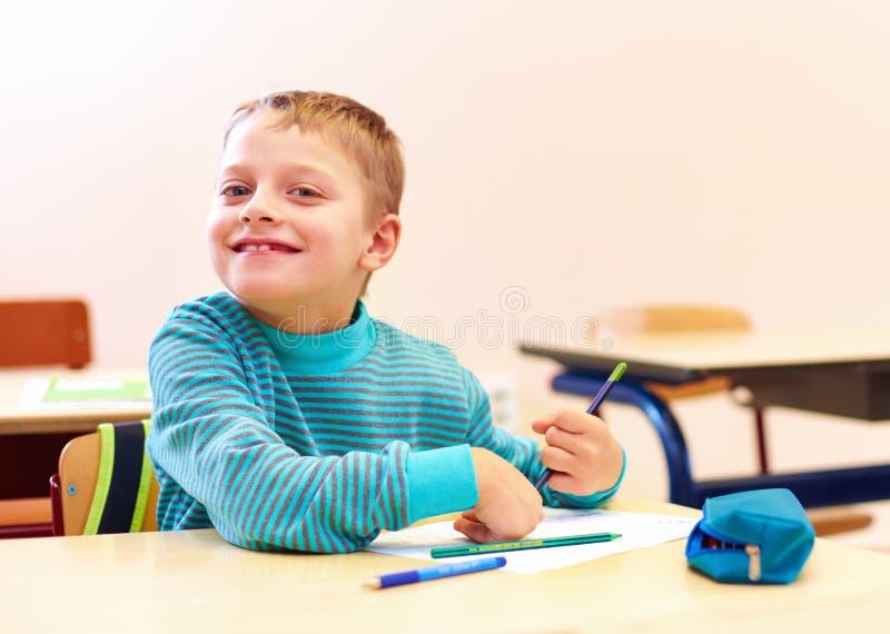 Netter Junge mit Special muss Briefe beim Sitzen am Schreibtisch im Klassenzimmer schreiben stockfoto