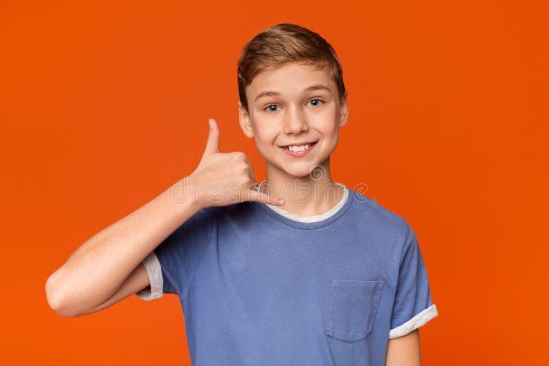 Netter Junge setzte seine Hand zu seinem Ohr und zu Lächeln lizenzfreies stockfoto