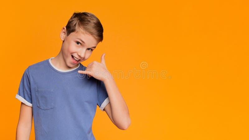 Netter Junge setzte seine Hand zu seinem Ohr und zu L?cheln lizenzfreie stockfotos