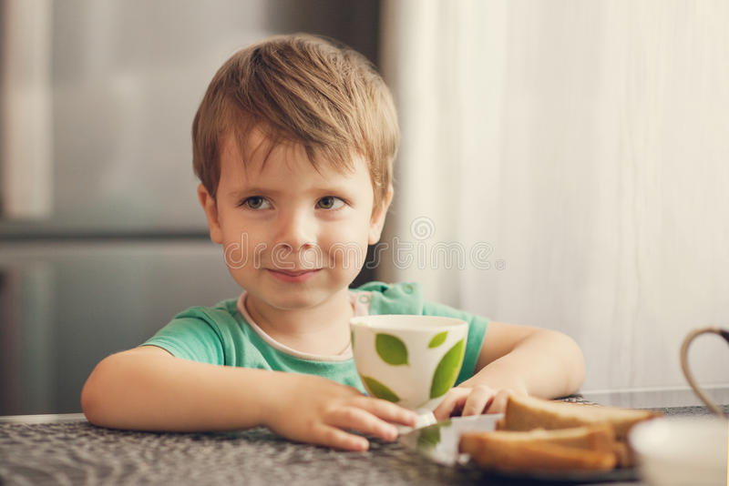 Netter Junge trinkt Milch, isst Toast zum Frühstück lizenzfreies stockbild