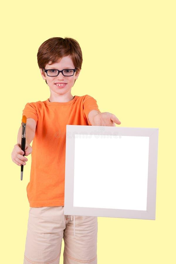 Netter Junge und glücklich mit einem Malerpinsel und einem unbelegten s lizenzfreie stockfotografie