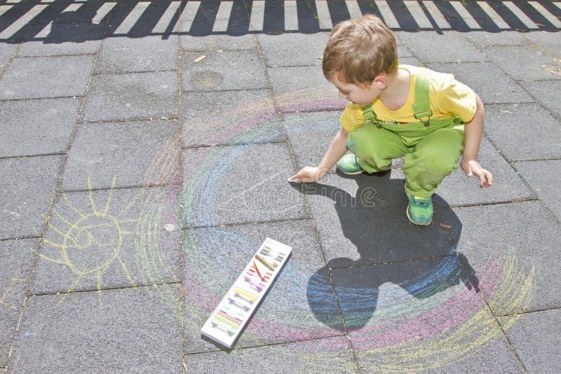 Netter Junge zeichnet mit bunten Kreiden auf Asphalt Sommertätigkeit und kreative Spiele für kleine Kinder Kind, das zusammen Spa stockfoto